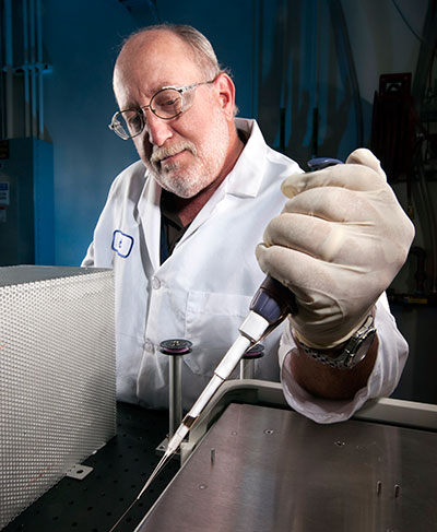 A scientist uses a pipette to process a liquid sample.